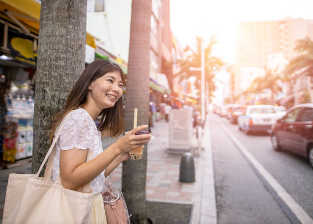 Young woman eating tart and drinking tapioca drink on street Young woman eating tart and drinking tapioca drink on street kokusai dori okinawa stock pictures, royalty-free photos & images