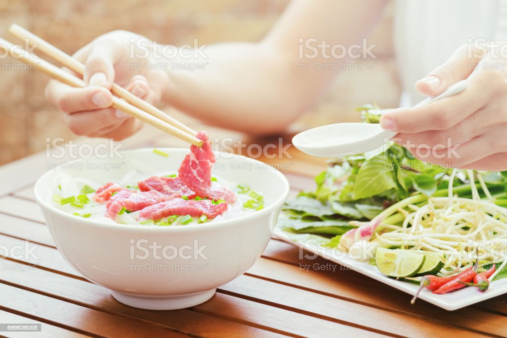 Young woman eating the Pho Bo in street cafe, Vietnam royalty-free stock photo