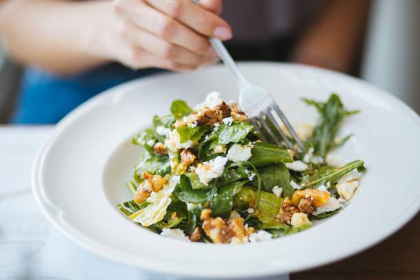 jovem mulher comer salada vegetariana no restaurante para o almoço - noz comida - fotografias e filmes do acervo