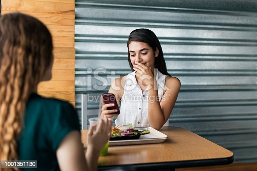 A young latin woman sitting at a table in a restaurant, eating with a female friend and using her mobile phone.