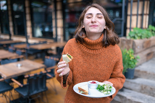 A young woman  eats a toast in a vegan fast food restaurant