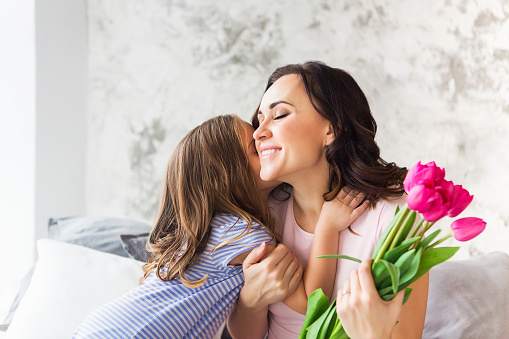 Young woman embrace with small girl