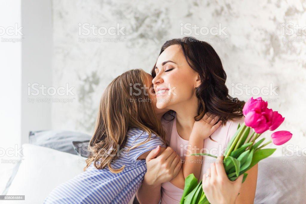 Young woman embrace with small girl stock photo