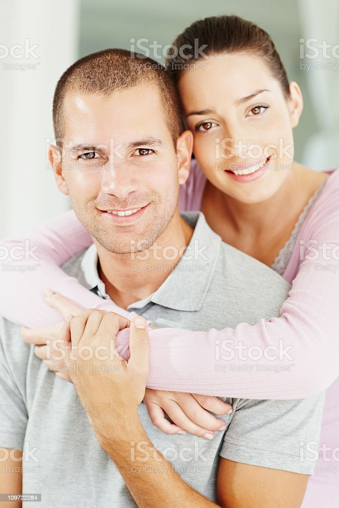Young woman embracing her husband from behind royalty-free stock photo