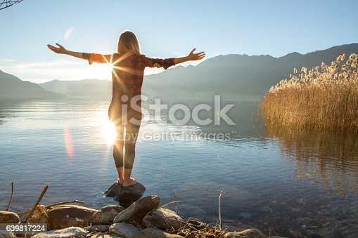 istock Young woman embracing nature, mountain lake 639817224