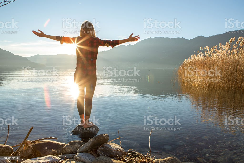 Young woman embracing nature, mountain lake stock photo