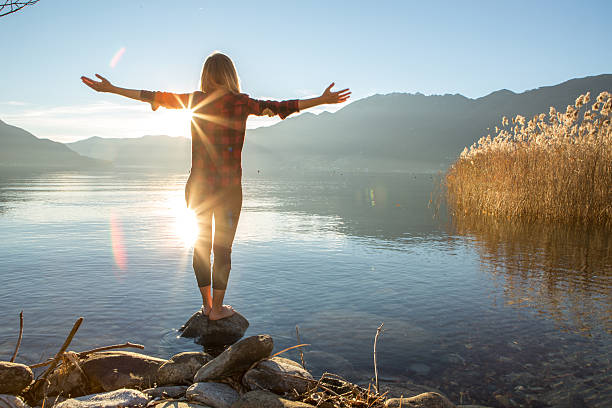 young woman embracing nature, mountain lake - holistic medicine stock photos and pictures