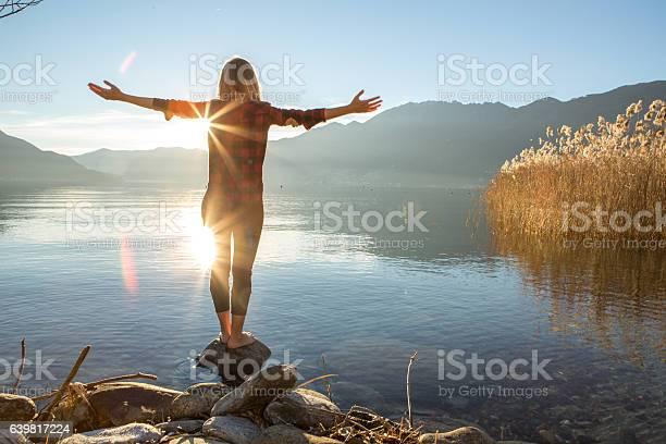 Photo of Young woman embracing nature, mountain lake