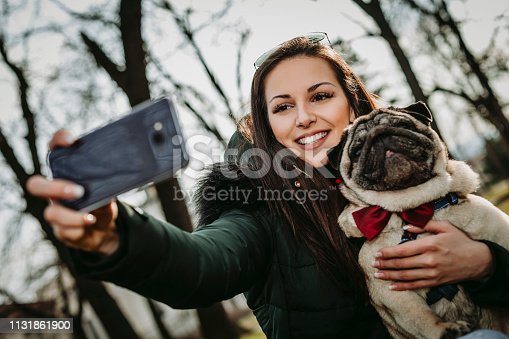 istock Young woman embracing pet dog in park 1131861900
