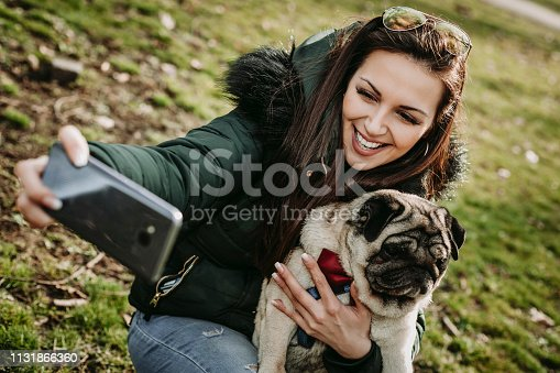 istock Young woman embracing pet dog in park 1131866360