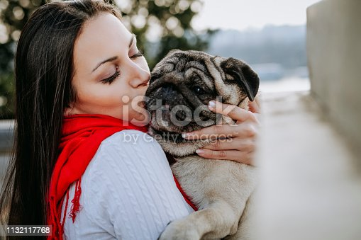 istock Young woman embracing pet dog in park 1132117768