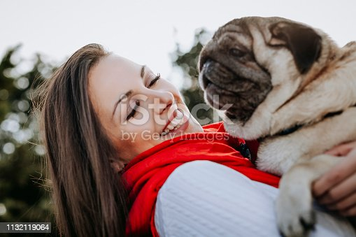 istock Young woman embracing pet dog in park 1132119064