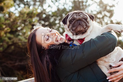 istock Young woman embracing pet dog in park 1132119586