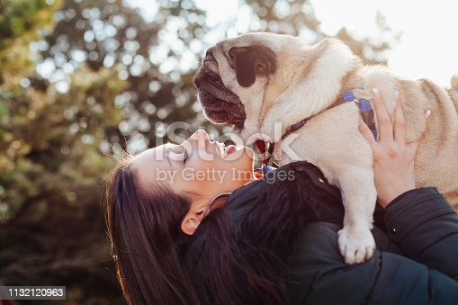 istock Young woman embracing pet dog in park 1132120963