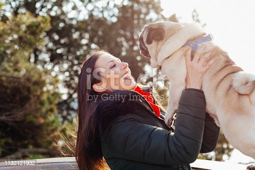 istock Young woman embracing pet dog in park 1132121932