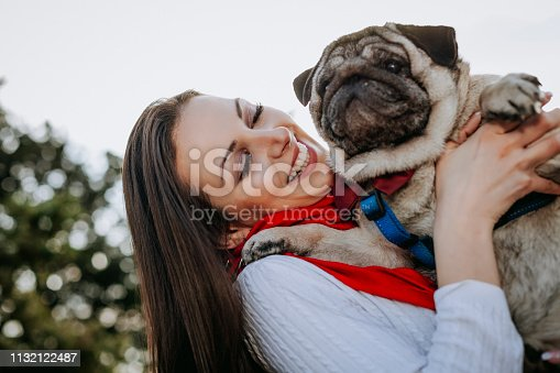 istock Young woman embracing pet dog in park 1132122487