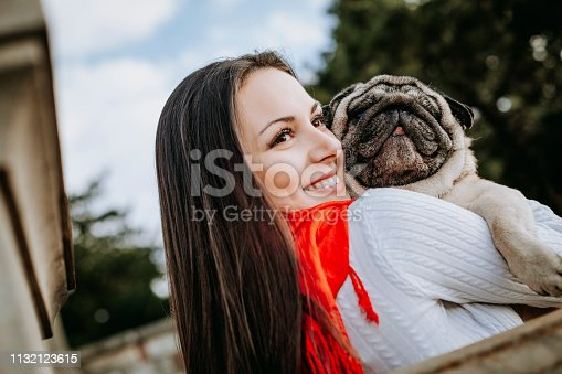 istock Young woman embracing pet dog in park 1132123615