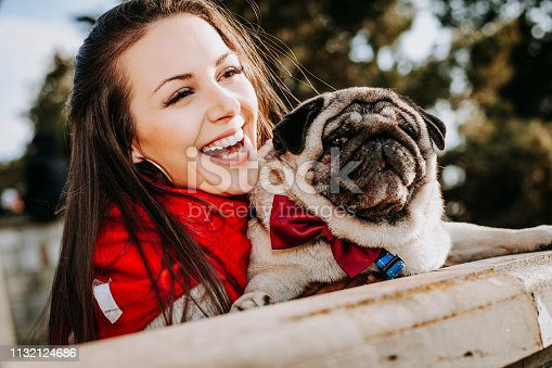 istock Young woman embracing pet dog in park 1132124686