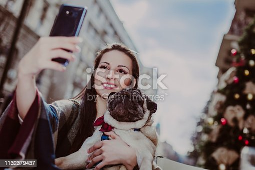 istock Young woman embracing pet dog in the city 1132379437