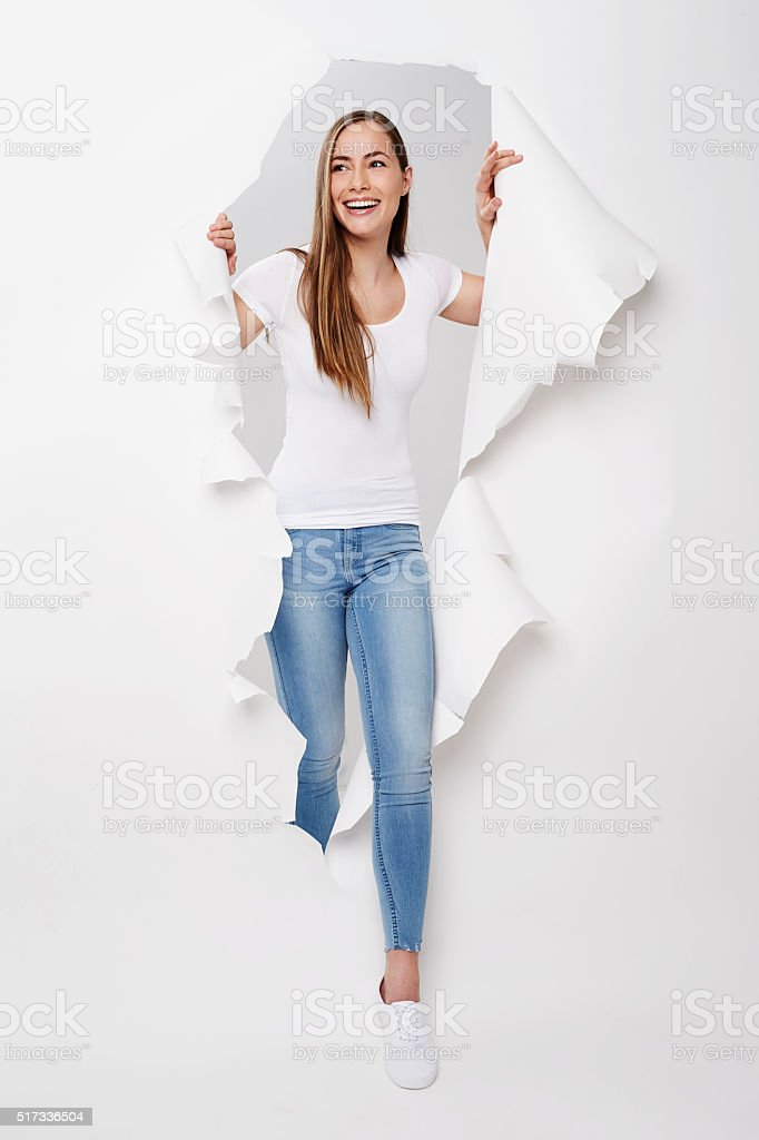 Young woman emerging from torn paper, smiling stock photo