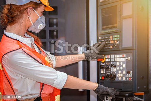 Young woman engineer in the mask protected herself with air pollution & virus with controller machine on blurred factory background