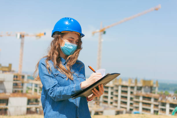 young woman engineer wearing face mask and holding clipboard with documents stock photo