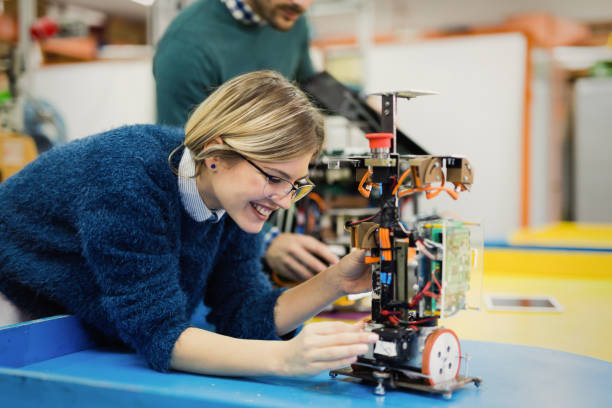 Young woman engineer working on robotics project stock photo