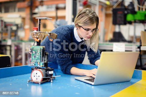 Young attractive woman engineer working on robotics project using laptop