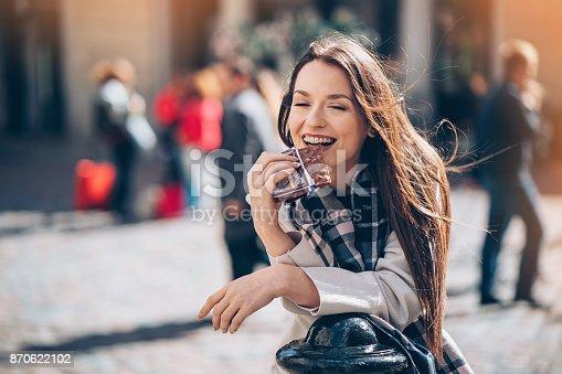 istock Young woman enjoying a chocolate bar outdoors 870622102