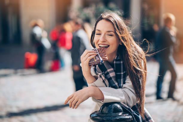 Young woman enjoying a chocolate bar outdoors stock photo