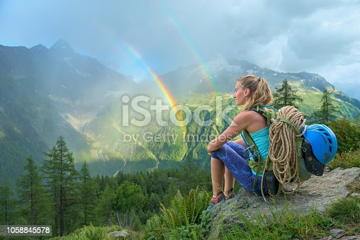 Young beautiful woman looking at a colorful double rainbow during summer rain in the mountains