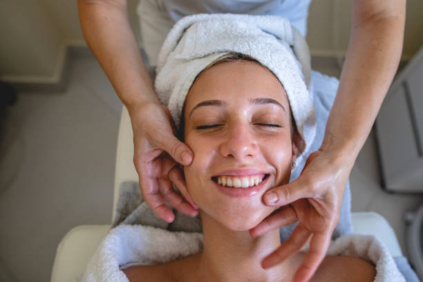 young woman enjoying a facial massage at a spa - chemical peel stock pictures, royalty-free photos & images