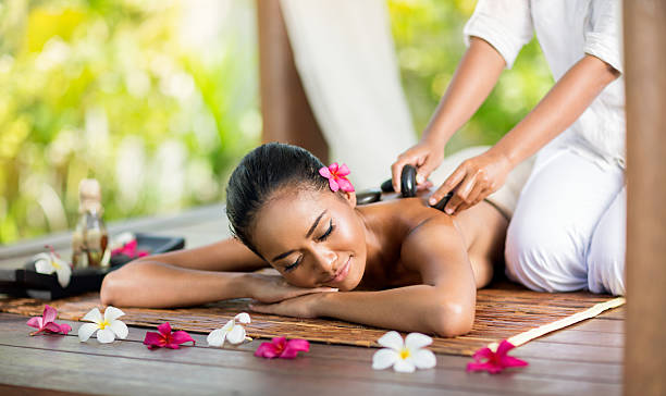 Young woman enjoying a hot stone massage Young Asian woman enjoying a hot stone massage lesser sunda islands stock pictures, royalty-free photos & images