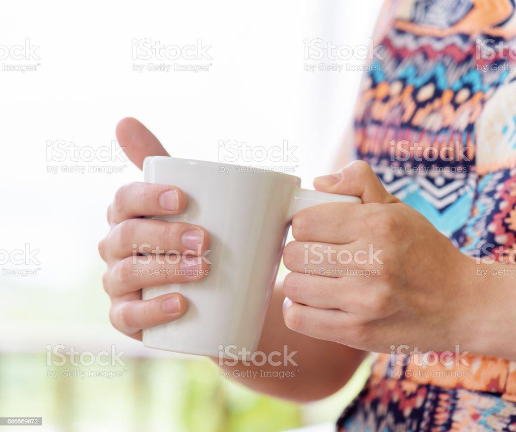 Young woman enjoying a mug of beverage. royalty-free stock photo