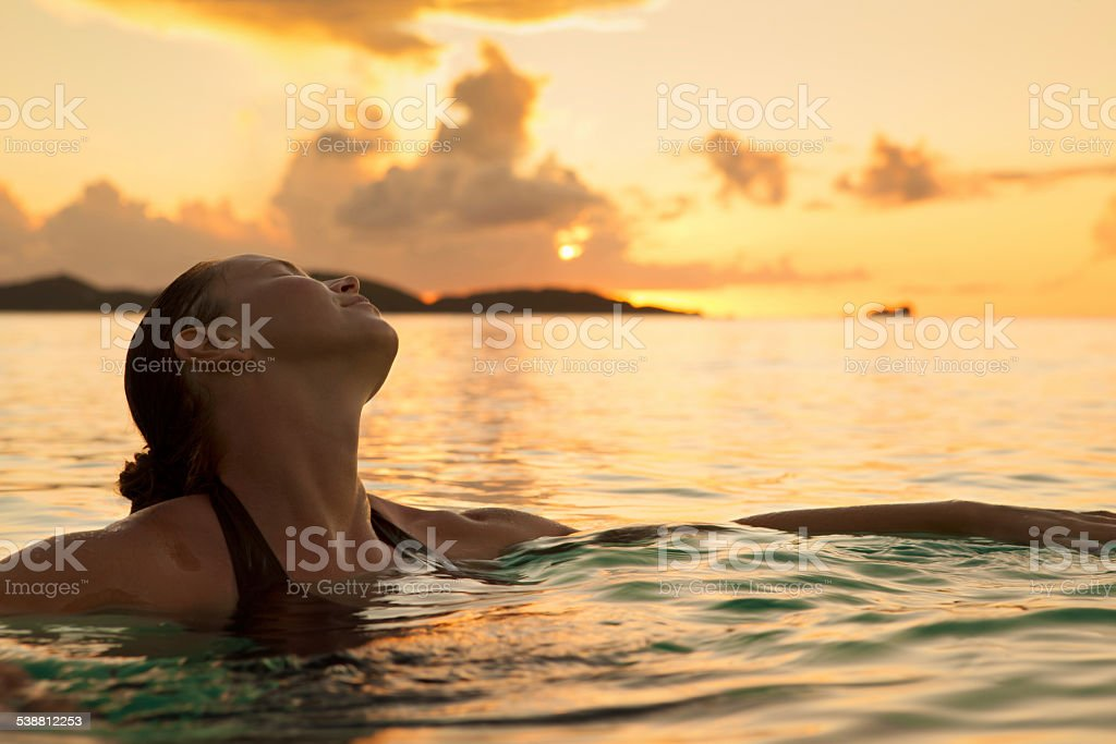 young woman enjoying a swim in Caribbean waters during sunset stock photo