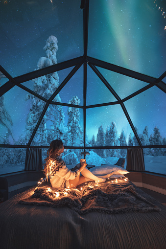 Young traveler woman standing on the comfortable bed and watching breathtaking northern lights or Aurora Borealis over a snowy landscape in starry night in Lapland, Finland