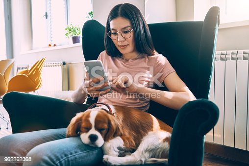 asian woman using smartphone with her dog sitting in her lap