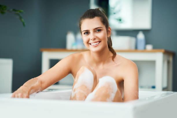 Junge Frau genießt und entspannt in der Badewanne – Foto