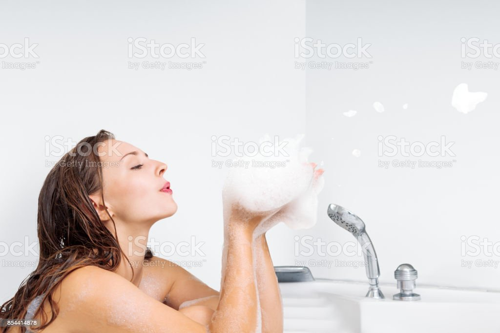 Young woman enjoying bathing in bathtub stock photo