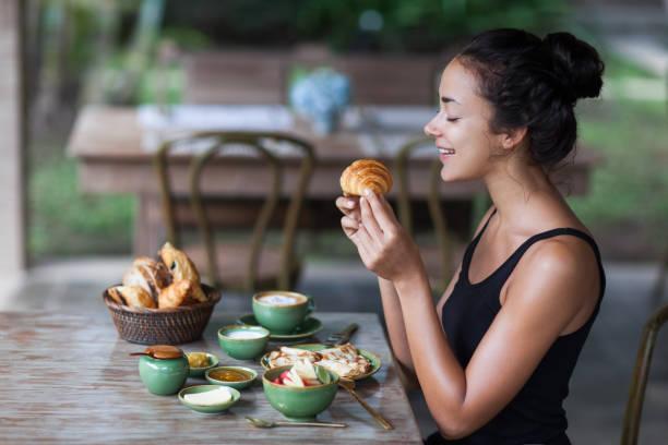 junge frau gefrühstückt und croissant in der hand halten. gute laune am morgen - ananas marmelade stock-fotos und bilder