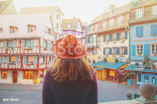 Young happy female enjoying Christmas in Old town illuminated and decorate magical like a fairy tale in Noel festive season in Colmar, Alsace, France