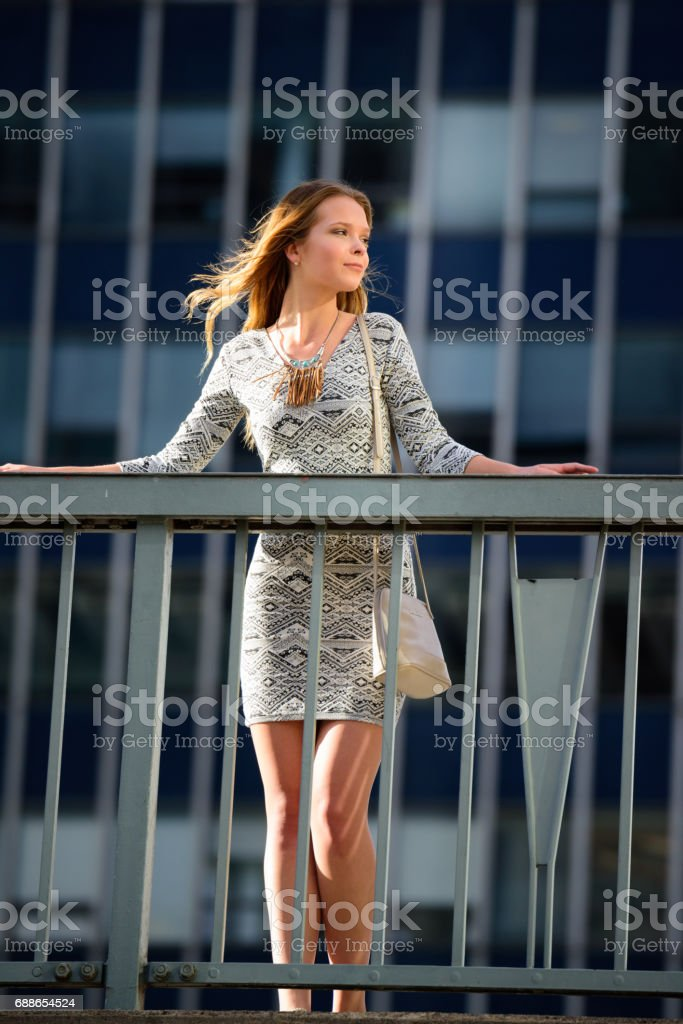 Young woman enjoying city sunset, hotorgsskraporna in background stock photo