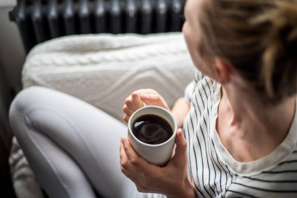 Young woman enjoying coffee and relaxing on a sofa stock photo