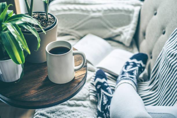 joven disfrutando de café y relajarse en un sofá con un libro - gente tranquila fotografías e imágenes de stock