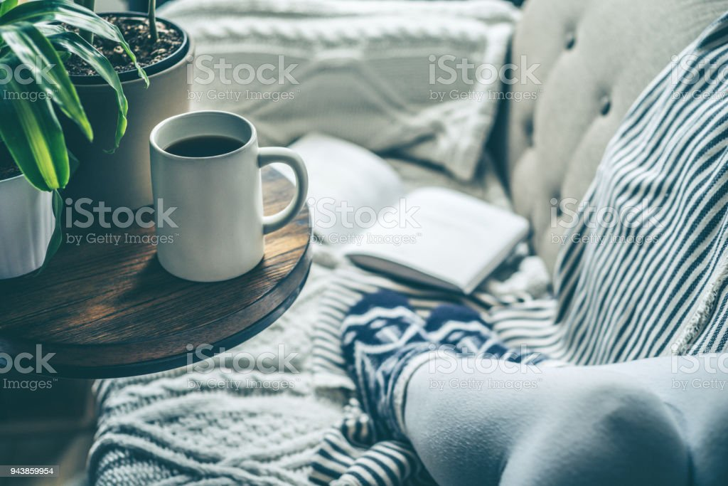 Young woman enjoying coffee and relaxing on a sofa with a book A young woman who is enjoying a cup of coffee while relaxing on a sofa. Conveys warmth and comfort in a relaxing environment. Adult Stock Photo