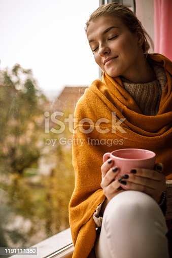 909062786 istock photo Young woman enjoying cold autumn day and warming her hands on a cup of tea 1191111380