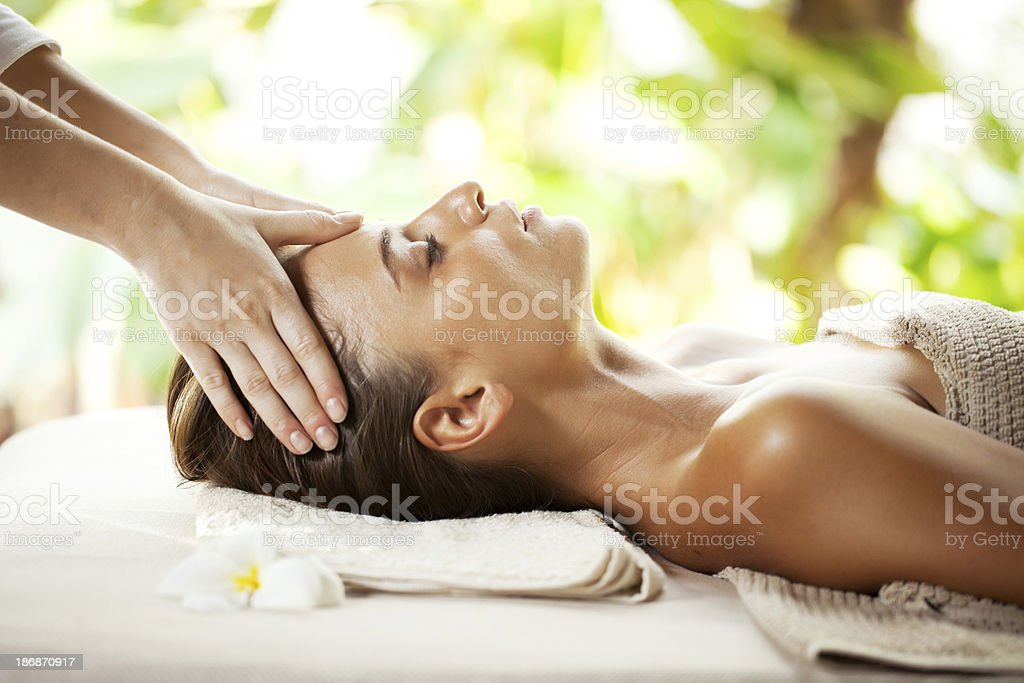 Young woman enjoying during head massage at tropical spa resort. stock photo
