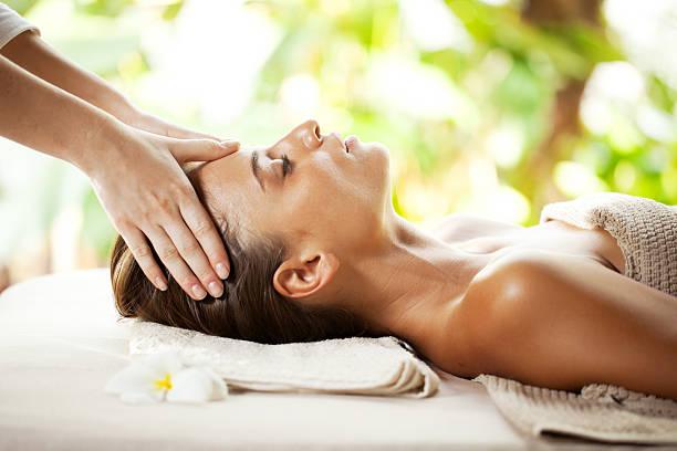 Young woman enjoying during head massage at tropical spa resort. stock photo