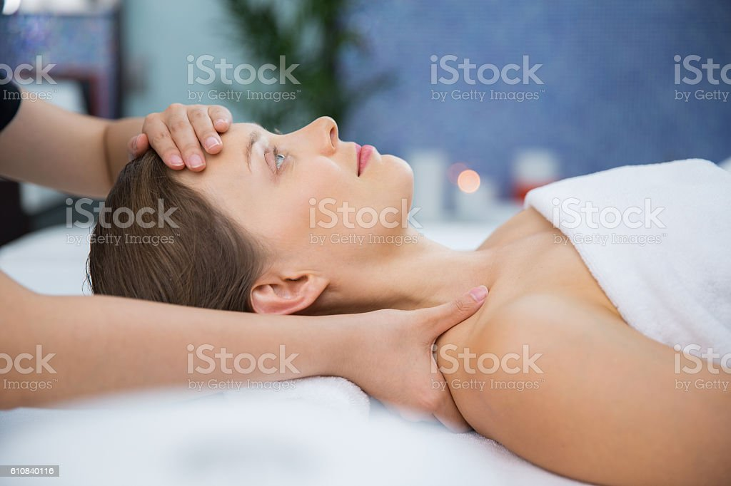 Young woman enjoying face and collar area massage stock photo