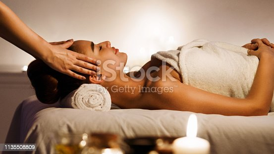 Young woman enjoying face massage with aromatic candles in spa salon